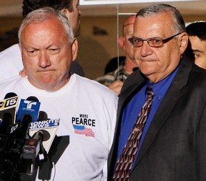 In this Nov. 8, 2011 file photo, Arizona State Sen. Russell Pearce, R-Mesa, left, prepares to address the media in Mesa, Ariz., after losing his recall election bid, as Maricopa County Sheriff Joe Arpiao, right, stands by his side. (AP Photo/Matt York, File)