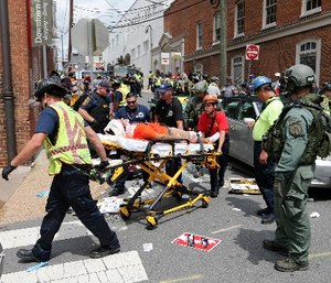 Rescue personnel help injured people after a car ran into a large group of protesters after an white nationalist rally in Charlottesville, Va., Saturday, Aug. 12, 2017. (AP Photo/Steve Helber)