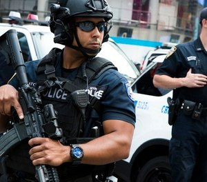 Members of the NYPD Counterterrorism Unit stand guard in Time Square as security is increased as a result of a attack in Barcelona, Spain earlier on Thursday, Aug. 17, 2017, at in New York. (AP Photo/Michael Noble Jr.)