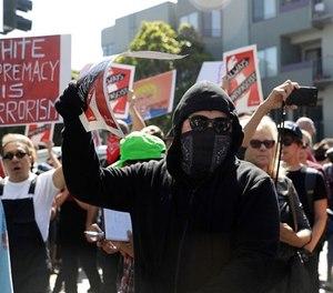 Protesters march outside of Alamo Square Park in San Francisco, Saturday, Aug. 26, 2017.