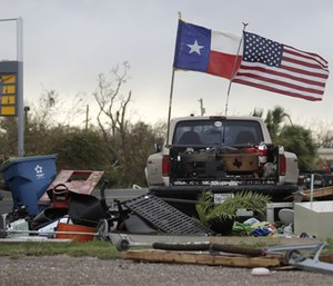 The Texas state flag and American flag wave in the wind over an area of debris left behind in the wake of Hurricane Harvey. (Photo/AP)