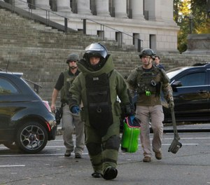 A member of the bomb squad carries a suitcase out of the Washington Capitol in Olympia, Wash., Monday, Oct. 23, 2017. Washington Gov. Jay Inslee's office was evacuated for a few hours after a woman dropped off a cartoon-themed suitcase she said was for the governor and ran out of the Capitol. (AP Photo/Rachel La Corte)