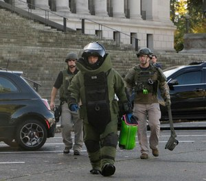 A member of the bomb squad carries a suitcase out of the Washington Capitol in Olympia, Wash., Monday, Oct. 23, 2017. Washington Gov. Jay Inslee's office was evacuated for a few hours after a woman dropped off a cartoon-themed suitcase she said was for the governor and ran out of the Capitol.