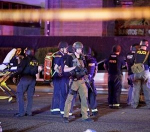 In this Oct. 2, 2017, file photo, police officers and medical personnel stand at the scene of the shooting near the Mandalay Bay resort and casino on the Las Vegas Strip in Las Vegas.