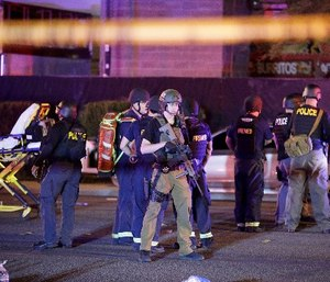 In this Oct. 2, 2017, file photo, police officers and medical personnel stand at the scene of a shooting near the Mandalay Bay resort and casino on the Las Vegas Strip in Las Vegas. (AP Photo/John Locher, File)