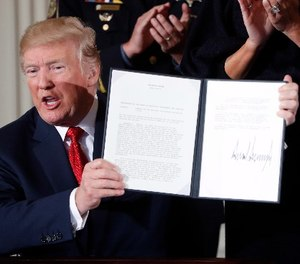 President Donald Trump displays a presidential memorandum he signed, declaring the opioid crisis a public health emergency in the East Room of the White House, Thursday, Oct. 26, 2017, in Washington. (AP Photo/Pablo Martinez Monsivais)
