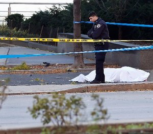A New York Police Department officer stands next to a body covered under a white sheet near a mangled bike along a bike path Tuesday Oct. 31, 2017, in New York.