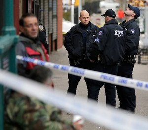 Police officers stand near the scene of a shooting in the Bronx section of New York, Tuesday, Dec. 5, 2017.