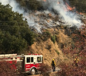In this photo provided by the Santa Barbara County Fire Department, an engine company from the city of Colton, Calif., operating under mutual aid, keeps watch on pockets of burning and unburned vegetation off Bella Vista Dr. in Montecito, Calif., Wednesday, Dec. 13, 2017. (Mike Eliason/Santa Barbara County Fire Department via AP)