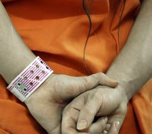 In this Dec. 10, 2013 an inmate wears his special purple wrist band in a new unit in the Harris County Jail for gay, bisexual and transgender inmates in Houston.