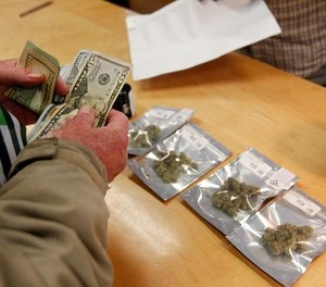 A customer purchases marijuana at Harborside marijuana dispensary, Monday, Jan. 1, 2018, in Oakland, Calif. (AP Photo/Mathew Sumner)
