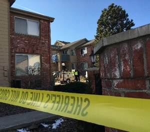 Sheriff's deputies remove a spotlight, Monday, Jan. 1, 2018, used to help investigators processing evidence at an apartment where Matthew Riehl fatally shot Douglas County Sheriff's Deputy Zackari Parrish and wounded six others in the Denver suburb of Highlands Ranch, on Sunday. (AP Photo/Colleen Slevin)