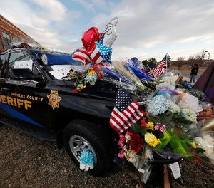 Tributes to a deputy killed in a shootout cover a patrol vehicle parked outside a Douglas County, Colo., Sheriffs Department substation Monday, Jan. 1, 2018, in Highlands Ranch, Colo.