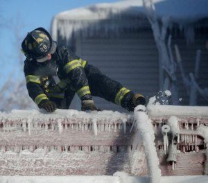 A firefighter kicks free a hose frozen onto a roof of a building after helping battle a five-building fire in Newark, N.J. (AP Photo/Julio Cortez)