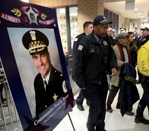 Chicago police officers pass a memorial portrait of Cmdr. Paul Bauer for a candlelight vigil for Bauer outside the Near North District headquarters Wednesday, Feb. 14, 2018, in Chicago. (AP Photo/Charles Rex Arbogast)