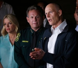 Florida Gov. Rick Scott, foreground, speaks along with Sheriff Scott Israel, center, of Broward County, and Pam Bondi, Florida Attorney General, during a news conference near Marjory Stoneman Douglas High School in Parkland, Fla., Wednesday, Feb. 14, 2018. (AP Photo/Wilfredo Lee)