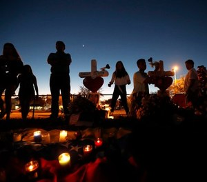 People visit a makeshift memorial outside Marjory Stoneman Douglas High School, where 17 students and faculty were killed in Wednesday's mass shooting in Parkland, Fla., Sunday, Feb. 18, 2018. (AP Photo/Gerald Herbert)