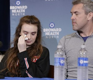 Marjory Stoneman Douglas High School shooting survivor Maddy Wilford, left, wipes a tear as her father David looks on during a press conference.