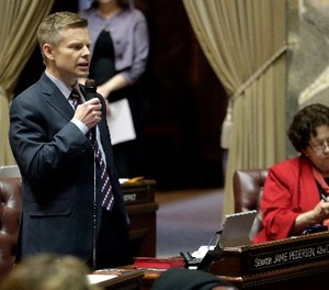 Sen. Jamie Pedersen, left, D-Seattle, speaks during debate on the Senate floor, Thursday, March 8, 2018, at the Capitol in Olympia, Wash., on the final day of the regular session of the Legislature. Lawmakers in the Senate were discussing a compromise measure designed to make it easier to prosecute police who commit reckless or negligent shootings in Washington state. (AP Photo/Ted S. Warren)