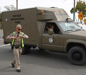 A sheriff's hostage negotiation team passes a checkpoint at the Veterans Home of California in Yountville, Calif. Authorities say a combat veteran shot himself in the head with a shotgun after fatally shooting three mental health workers on March 9, 2018. (AP Photo/Ben Margot, File)