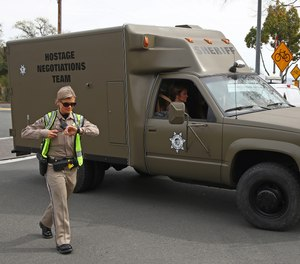 A sheriff's hostage negotiation team passes a checkpoint at the Veterans Home of California in Yountville, Calif. Authorities say a combat veteran shot himself in the head with a shotgun after fatally shooting three mental health workers on March 9, 2018.