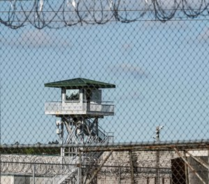 In this April 16, 2018, file photo, a guard tower stands above the Lee Correctional Institution, a maximum security prison in Bishopville, S.C., where a number of South Carolina corrections employees faced federal charges related to bribery and bringing contraband into the state's institutions a week after a deadly riot. (AP Photo/Sean Rayford, File)