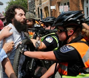 A demonstrator confronts police on the anniversary of the Unite the Right rally in Charlottesville, Va., Sunday, Aug. 12, 2018.