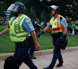 Washington Metropolitan Police in riot gear walk near the White House on the one year anniversary of the Charlottesville