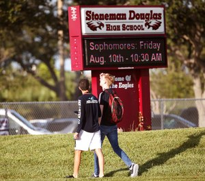 Student walk to class at Marjory Stoneman Douglas High School, Wednesday, Aug. 15, 2018, in Parkland, Fla. Students at the school returned Wednesday, to a more secure campus as they began their first new school year since a gunman killed 17 people in the freshman building.