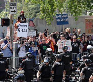 Police form a barrier to keep counter-protesters separated from members of Patriot Prayer and other groups supporting gun rights march during a rally, Saturday, Aug. 18, 2018, at City Hall in Seattle. (AP Photo/Ted S. Warren)
