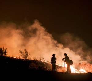 In this Aug. 9, 2018, file photo, firefighters keep watch the Holy Fire burning in the Cleveland National Forest in Lake Elsinore, Calif. (AP Photo/Ringo H.W. Chiu, File)