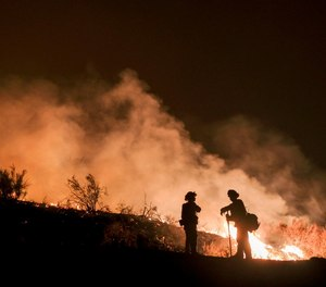 In this Aug. 9, 2018, file photo, firefighters keep watch the Holy Fire burning in the Cleveland National Forest in Lake Elsinore, Calif.
