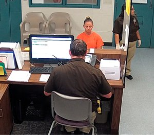 This photo from video released Thursday, Sept. 13, 2018, by the Kaufman County Sheriff's Office in Kaufman, Texas, shows Dallas police Officer Amber Guyger getting booked after turning herself in Sunday, Sept. 9 following the fatal shooting of Botham Jean in his own apartment. Guyger was arrested manslaughter and has since been released on bond.