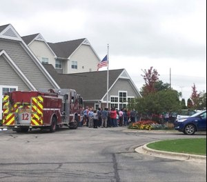 A fire truck and people evacuated are gathered at a hotel near the scene after a shooting was reported at a software company in Middleton, Wis., Wednesday, Sept. 19, 2018. Multiple were reported to have been shot.
