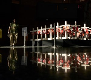 In this Friday, Sept. 21, 2018, photo, a man walks by crosses on display at the Clark County Government Center in Las Vegas. The crosses had been part of a makeshift memorial along the Las Vegas Strip erected in memory of the victims of the Oct. 1, 2017 mass shooting at a country music festival in Las Vegas.  (AP Photo/John Locher)