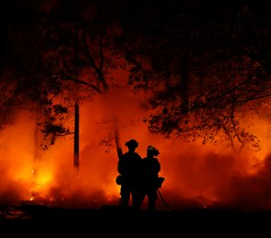 Firefighters work on a controlled burn at the Camp Fire, Friday, Nov. 9, 2018, in Magalia, Calif. (AP Photo/John Locher)