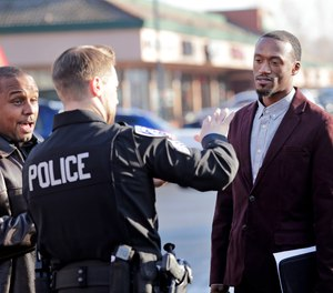 Byron Ragland, second right, talks with Kirkland police Sgt. Eric Karp near a frozen-yogurt shop that Ragland was kicked out of weeks earlier, Tuesday, Nov. 20, 2018, in Kirkland, Wash. The police department has apologized for an incident in which officers helped the owner of the Menchie's shop expel Raglandfrom the business because employees said they felt uncomfortable.