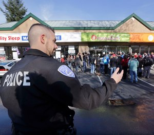 A Kirkland police officer directs traffic past a shop where Byron Ragland and local civil rights leaders addressed media members Tuesday, Nov. 20, 2018, in Kirkland, Wash. The police department there has apologized for an incident in which officers helped the owner of the Menchie's shop expel Ragland, an African-American man, from the business because employees said they felt uncomfortable.