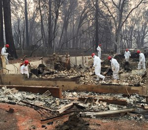 In this Nov. 15, 2018 file photo, volunteer rescue workers search for human remains in the rubble of homes burned in the Camp Fire in Paradise, Calif. A northern California sheriff's office has released the names of two more people who died in a devastating wildfire that killed at least 86 people. The Butte County Sheriff's office identified on Thursday, Jan. 31, 2019, the deceased as 74-year-old Robert Quinn of Paradise and 93-year-old Berniece Schmidt of Magalia.
