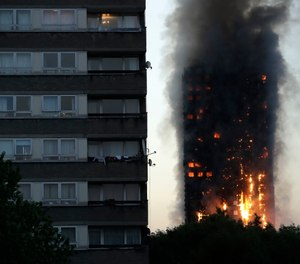 In this Wednesday, June 14, 2017 file photo, smoke and flames rise from the Grenfell Tower, in London. Police investigating a blaze that killed 72 people in a London tower block two years ago say no one is likely to face criminal charges until 2021. (AP Photo/Matt Dunham, File)