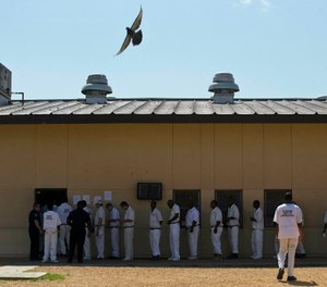 In this June 18, 2015, file photo, prisoners stand in a crowded lunch line during a prison tour at Elmore Correctional Facility in Elmore, Ala. (AP Photo/Brynn Anderson, File)