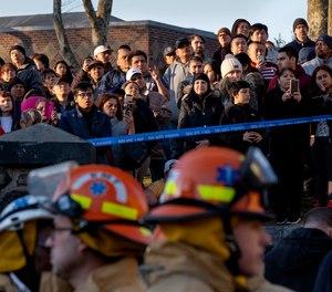 People watch as FDNY firefighters battle a multi-alarm fire in Brooklyn.