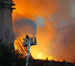A fire fighter uses a hose as Notre Dame cathedral is burning in Paris, Monday, April 15, 2019. (AP Photo/Francois Mori)