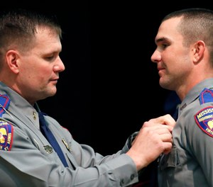 Cadet Jonathan Mark Steed, right, smiles as his father, Mississippi Bureau of Investigation Lt. Mark Steed, left, has difficulty in pinning the Mississippi Highway Patrol badge on him, Wednesday, May 1, 2019, during their graduation ceremony, in Pearl, Miss. (AP Photo/Rogelio V. Solis)