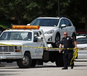 A vehicle belonging to the Virginia Beach active shooting suspect is removed from a parking lot outside the municipal building that was the scene of the shooting.