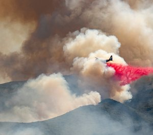 A plane drops fire retardant on a hillside in an attempt to box in flames from a wildfire during the Sand Fire in Rumsey, Calif.