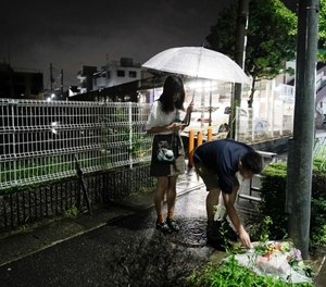 A couple places flowers near the Kyoto Animation building that was destroyed in an arson attack in Kyoto, Japan. (AP Photo/Jae C. Hong)