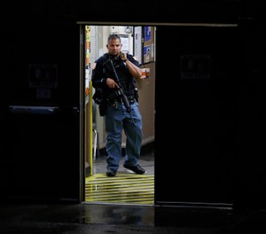 A police officer stands in the doorway to a Walmart where a gunman opened fire in a shopping complex Saturday, Aug. 3, 2019, in El Paso, Texas. (AP Photo/John Locher)