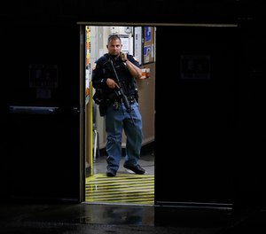 A police officer stands in the doorway to a Walmart where a gunman opened fire in a shopping complex Saturday, Aug. 3, 2019, in El Paso, Texas.