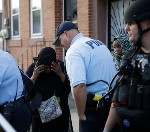 A police officer comforts a bystander near the scene of a shooting on Wednesday, Aug. 14, 2019, in Philadelphia where a gunman opened fire on police as they were serving a warrant, wounding several officers.